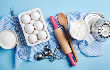 Preparation for baking. Ingredients and kitchen items for baking. Kitchen utensils, flour, eggs, sugar. Top view.