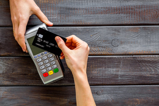 Contactless payment, paypass. Hand hold bank card near terminal on dark wooden background top-down copy space
