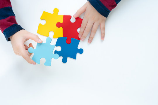 Top view, hands of an autistic child play colorful puzzle which is a symbol of public awareness for autism spectrum disorder - World Autism Awareness day on April 2, Understanding and Acceptance.