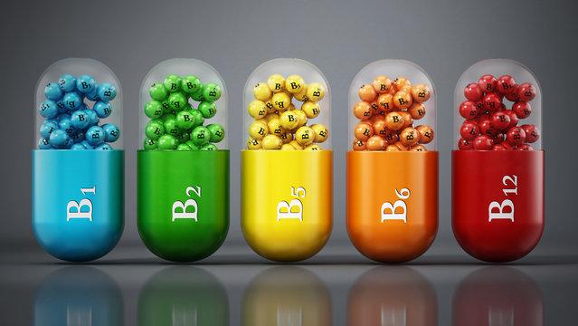Various vitamin B pills standing on dark gray background. 3D illustration