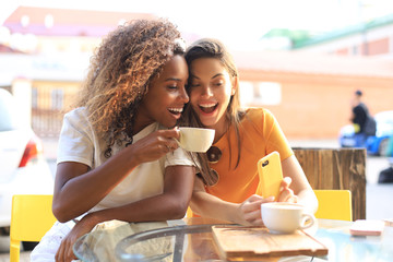 Two beautiful young woman sitting at cafe drinking coffee and looking at mobile phone.
