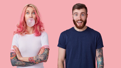 Portrait of open-eyed young lovely tattooed pair dressed in casual t-shirts posing over pink background, looking amazedly to camera with raised eyebrows