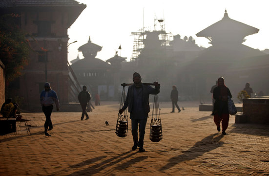 A man carrying yogurt in earthen pots for sale, walks through the premises of Bhaktapur Durbar Square in Bhaktapur