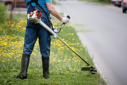 View from the back to the man with a gasoline mower. Worker in overalls mows the grass on the lawn with a trimmer near the roadway.