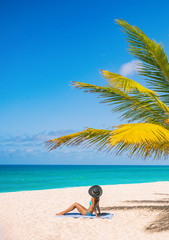 Photo sur Toile Les Textures Caribbean beach tourist relaxing in Barbados, cruise shore day. Woman sunbathing sun tanning under palm tree on sand on Dover beach, famous resort tourist tropical destination.