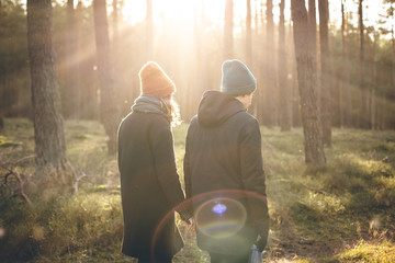 Couple in warm clothing taking a walk inside a sunny forest