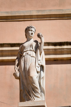 Marble statue of a woman on a facade in Cagliari.