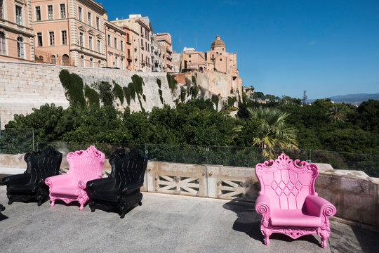 Four black and pink plastic armchairs on a terrace