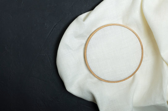 Top view of wooden embroidery hoop, white clean evenweave fabric on the black table.Empty space for design