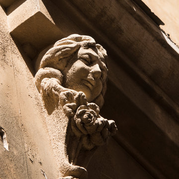Detail of an anonymous sculpture on a wall house. A girl with long hair braids and round-cheeked smiling is carved in a white stone.