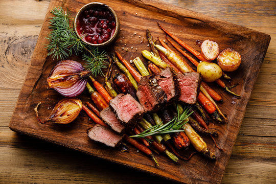 Grilled sliced Venison Steak with baked vegetables and berry sauce on wooden background