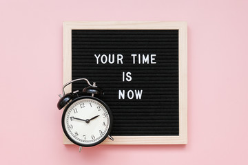 Your time is now. Motivational quote on letter board and black alarm clock on pink background. Top...