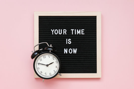 Your time is now. Motivational quote on letter board and black alarm clock on pink background. Top view Flat lay Concept inspirational quote of the day.