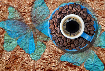 brazilian coffee. blue cup of coffee with roasted coffee beans on a saucer. cup of coffee on a...
