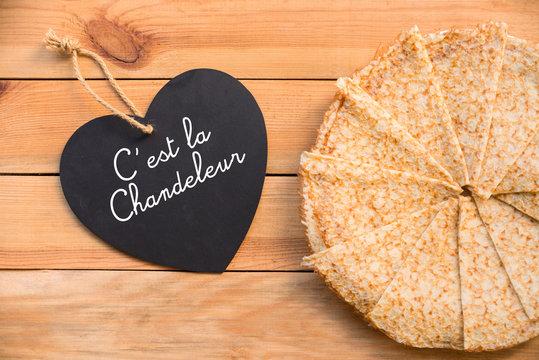 Assiette de crêpes, message c'est la Chandeleur écrit que un ardoise coeur, fond rustique en bois