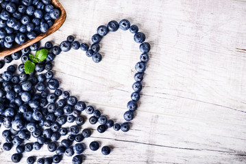 Freshly picked blueberries in wooden bowl on white table. Juicy and fresh blueberry with green...