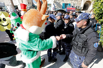 Person wearing a costume of a cartoon character hands sweets to a Palestinian policeman during Christmas celebrations according to the Eastern Orthodox calendar, at Manger Square in Bethlehem, in the Israeli-occupied West Bank