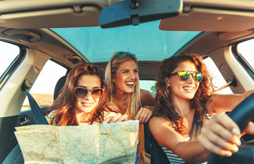 Three female friends enjoying traveling at vacation in the car. Fotomurales