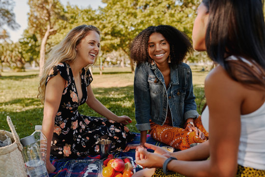 Group of smiling multiracial female best friends sitting together on blanket with fruits enjoying at picnic in the park - group of healthy friends having a picnic