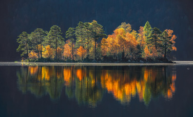 Charming autumn landscape of islands with pine-trees in the middle of Eibsee lake.