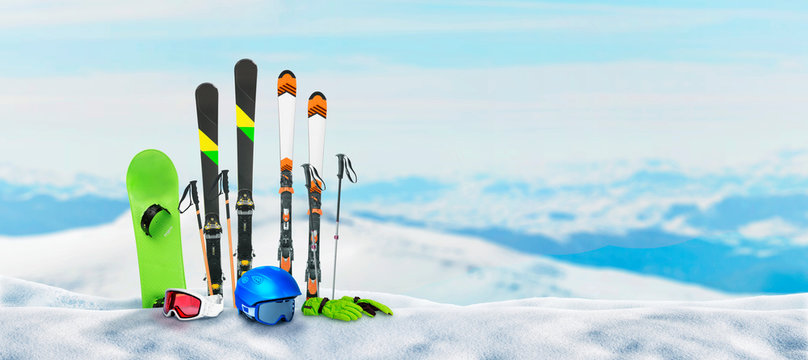 Ski equipment pinned to the snow on top of a mountain. Concept of winter holidays and snow sports. Snowy mountain peaks in the background