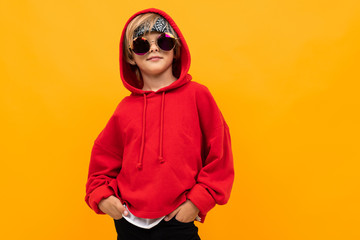 blond boy with a bandana on his head in a red hoodie and glasses posing on an orange background