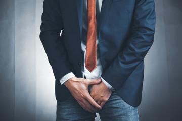 man holding his crotch on dark background
