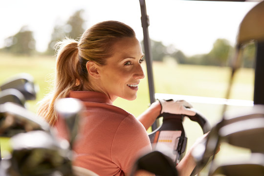 Rear View Of Mature Woman Playing Golf Driving Buggy Along Course Viewed Through Golf Clubs