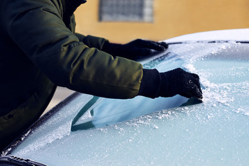 Man scraping ice from the windshield of a car covered wit hoarfrost