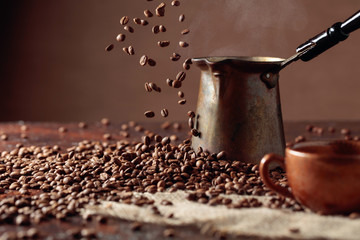 Falling coffee beans and old copper coffee maker.