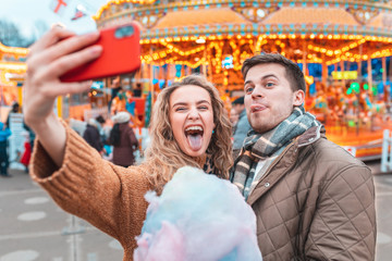 Ingelijste posters Amusementspark Couple having fun and taking a selfie at amusement park in London