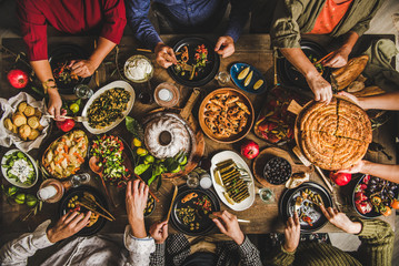 Traditional Turkish family celebration dinner. Flat-lay of people feasting at table with Turkish salads, cooked vegetables, meze starters, pastries and raki drink, top view. Middle Eastern cuisine Fototapete