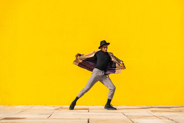Young man dancing in front of yellow wall