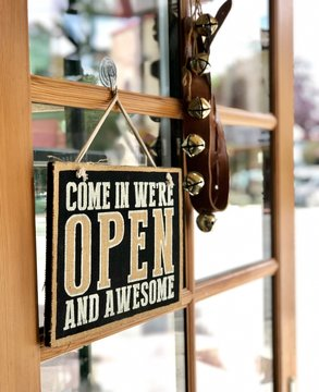 Come in we are open sign and bells are hanging on the door of a small retail business