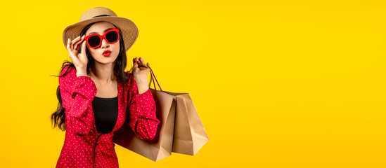 Banner of Asian trendy shopaholic woman excited about new purchases or sales holding shopping bags and looking to camera over yellow background. Happy Asian customer carrying shopping bags.
