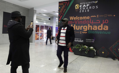 A CAF official poses for a picture at Hurghada International Airport in front of banner for the upcoming CAF Awards ceremony, in Hurghada