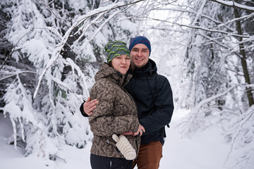 Fototapete - Young couple smiling while hiking in a snow covered forest