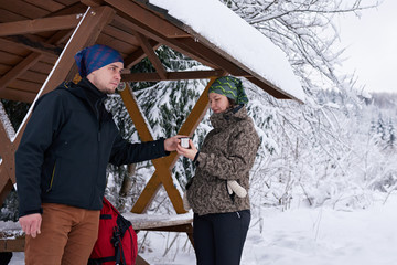 Fototapete - Adventurous couple sharing coffee while out for a winter hike