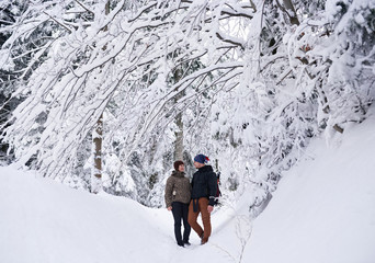 Fototapete - Smiling couple standing in a snowy forest while out hiking