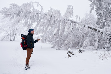 Fototapete - Young man taking photos of a snow covered winter landscape