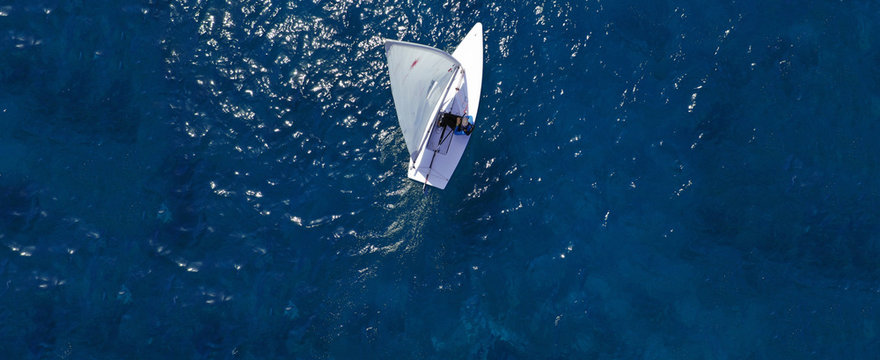 Aerial drone ultra wide photo of children practising with small sail boats in Mediterranean bay with deep blue sea