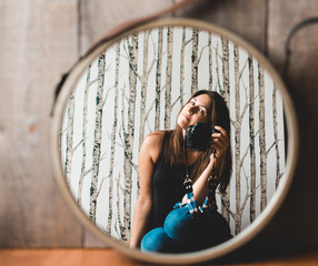 Woman holding camera taking photo of her reflection in the mirror.