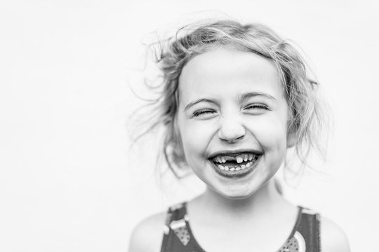 A portrait of a little girl missing her front tooth.
