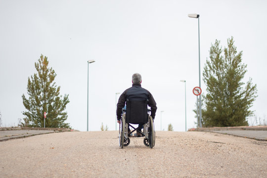 Rear vision of a disabled man in a wheelchair alone in the street