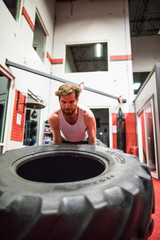 Fit man lifting large tire in gym