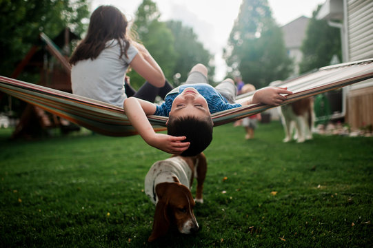 Siblings relaxing in hammock together while dog walks underneath