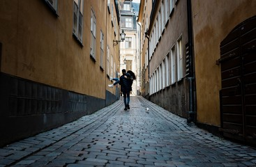 man holding his girlfriend whilst walking in the streets in Europe