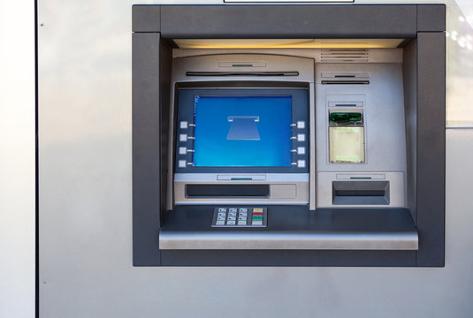 Silver atm machine with screen and buttons is in building wall, nobody