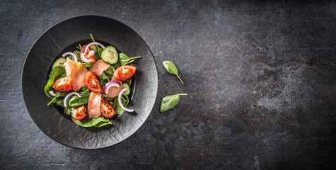 Salmon salad with vegetable in plate on dark kitchen table - Top of view