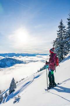 nice senior woman snowshoeing on the Nagelfluh chain above a sea of fog over Bregenz Wald mountains, Hochgrat, Steibis,Bavarian alps,